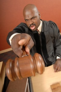 Upset judge pointing at the viewer with a gavel while shouting